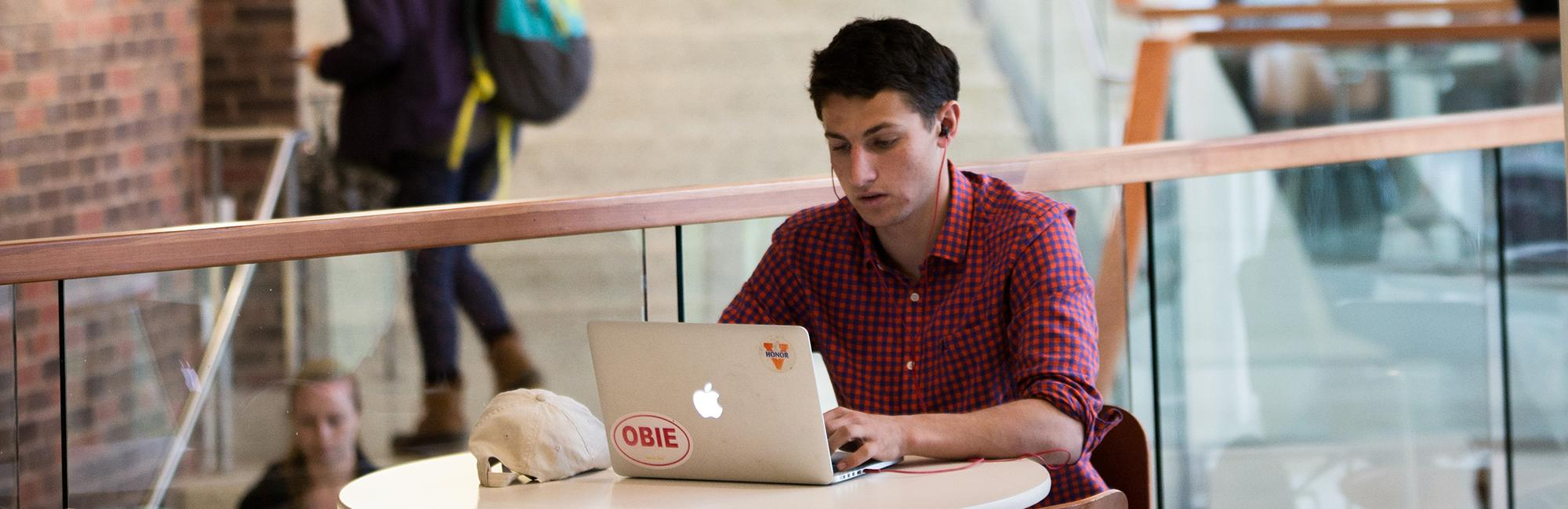 Male student sitting at table using a laptop